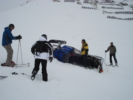 Skiers helping to roll back a snowmobile