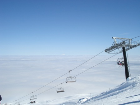 Skiing and chairlifts above the clouds